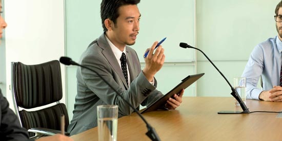 Professional speaking into Shure mic at a meeting