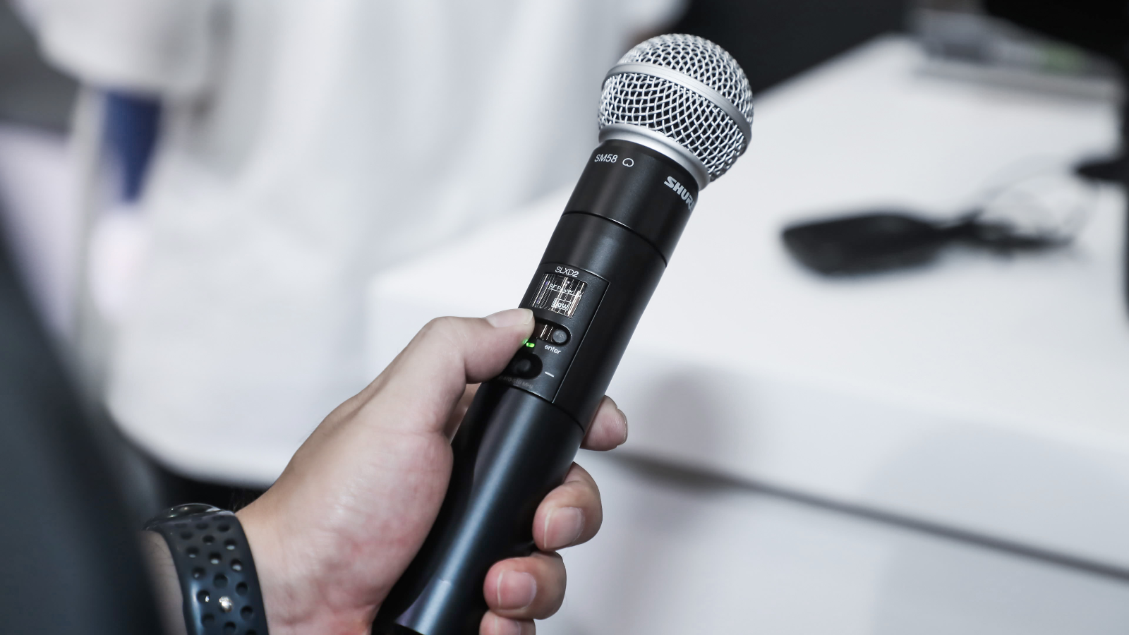 person holding SLXD2 wireless microphone