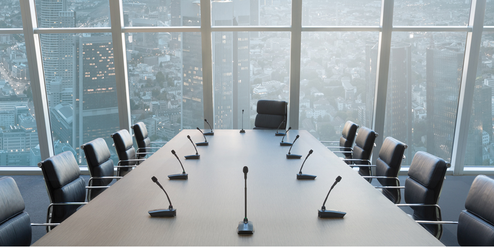 Modern boardroom with Shure mics and large windows overlooking city